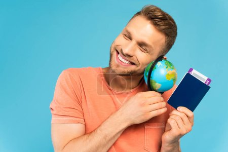 happy bearded man with closed eyes holding passport and globe isolated on blue