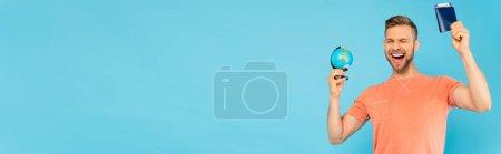 Photo pour Concept panoramique d'homme barbu excité avec les yeux fermés tenant passeport et globe isolé sur bleu - image libre de droit