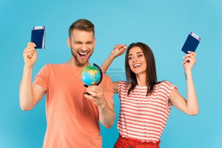 cheerful couple looking at globe while holding passports isolated on blue