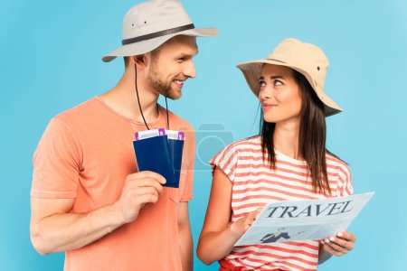 Photo for Happy girl in hat holding travel newspaper and looking at man with passports isolated on blue - Royalty Free Image