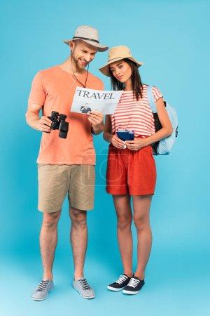 glückliche Reisende in Hüten lesen Reisezeitung auf blau
