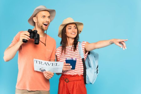 Photo for Happy girl pointing with finger and holding passports near excited man with travel newspaper and binoculars isolated on blue - Royalty Free Image