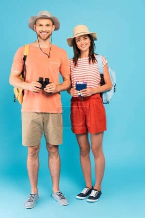 Photo for Happy girl holding passports near cheerful man with binoculars standing on blue - Royalty Free Image