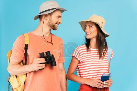 happy travelers in hats looking at each other while holding passports and binoculars isolated on blue