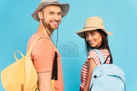 Photo for Happy travelers in hats looking at camera isolated on blue - Royalty Free Image