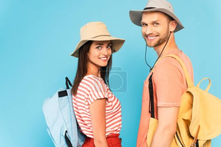 happy couple in hats with backpacks looking at camera isolated on blue