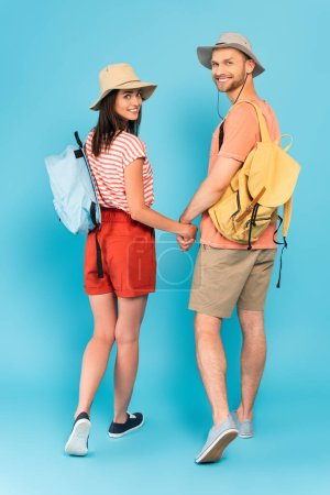 happy couple with backpacks holding hands and looking at camera on blue