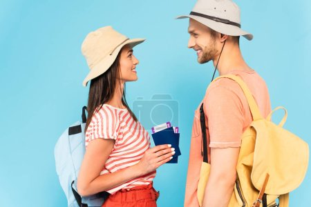 Photo for Side view of happy woman in hat holding passports near cheerful boyfriend isolated on blue - Royalty Free Image