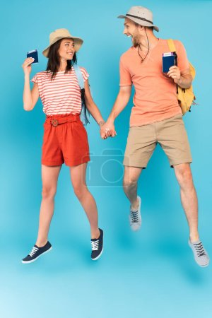 cheerful couple in hats holding hands and passports while jumping on blue