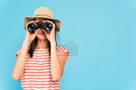 young woman in hat looking through binoculars isolated on blue