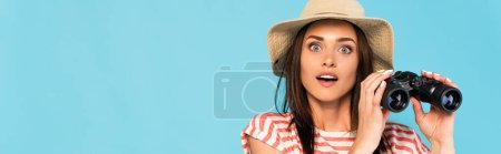 panoramic shot of young surprised woman in hat holding binoculars isolated on blue