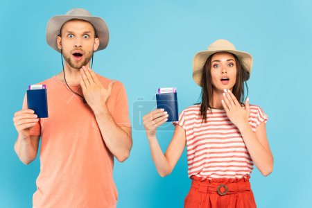 surprised man and woman in hats looking at camera and holding passports on blue