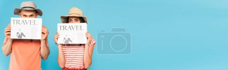 panoramic crop of couple in hats covering faces with travel newspapers isolated on blue