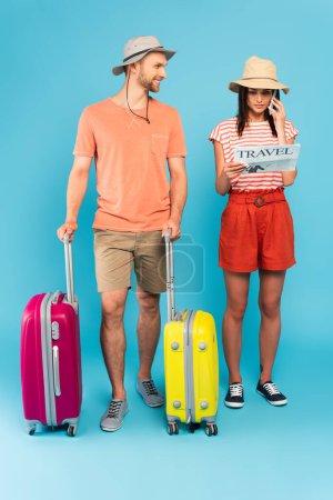 hombre barbudo feliz de pie con el equipaje y mirando a la chica leyendo el periódico de viaje y hablando en el teléfono inteligente en azul