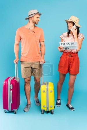 bärtiger Mann steht mit Gepäck da und schaut fröhliches Mädchen an, das Reisezeitung liest und auf blauem Smartphone spricht