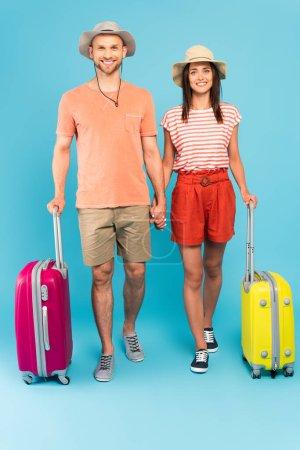 glückliches Paar in Hüten neben Reisetaschen stehend und Händchen haltend auf blauem Grund