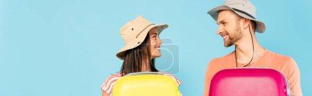 Photo pour Plan panoramique de couple heureux se regardant et tenant des bagages isolés sur bleu - image libre de droit