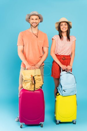 happy couple in hats standing with luggage and backpacks on blue