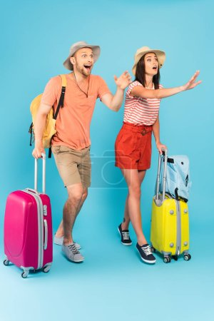 emotional couple in hats standing with luggage and gesturing on blue