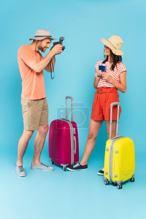 Photo for Happy man in hat taking photo of girl with passports while holding vintage camera and standing near luggage on blue - Royalty Free Image