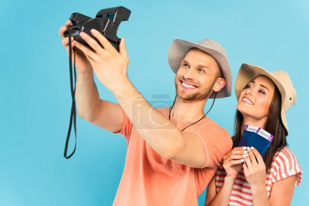 Photo for Happy man in hat holding vintage camera and taking selfie with cheerful girl isolated on blue - Royalty Free Image