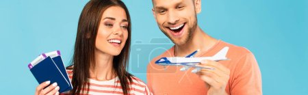 panoramic crop of happy girl holding passports and looking at toy plane in hand of bearded man isolated on blue