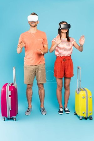 Photo for Cheerful couple in virtual reality headsets standing with luggage on blue - Royalty Free Image