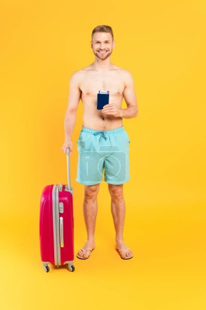 Photo pour Homme heureux et musclé tenant passeport et debout avec des bagages sur jaune - image libre de droit