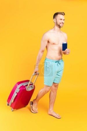 Photo pour Homme heureux et musclé tenant un passeport et marchant avec des bagages sur jaune - image libre de droit