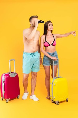 muscular looking through binoculars and standing near baggage and girl pointing with finger on yellow