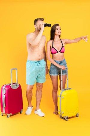 Photo pour Musclé regardant à travers les jumelles et debout près des bagages et la fille pointant du doigt sur jaune - image libre de droit