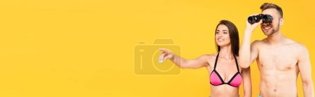 website header of cheerful woman pointing with finger while shirtless man looking through binoculars isolated on yellow
