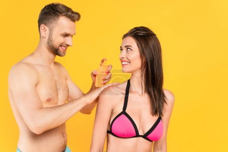 Photo for Shirtless man smiling while applying sunblock on cheerful woman isolated on yellow - Royalty Free Image