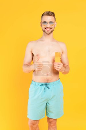 happy shirtless man in sunglasses showing thumb up and holding bottle with sunblock isolated on yellow