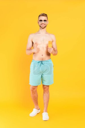 Photo for Happy shirtless man in sunglasses showing thumb up and holding bottle with sunblock on yellow - Royalty Free Image