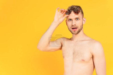 Photo for Shocked and shirtless man touching sunglasses isolated on yellow - Royalty Free Image