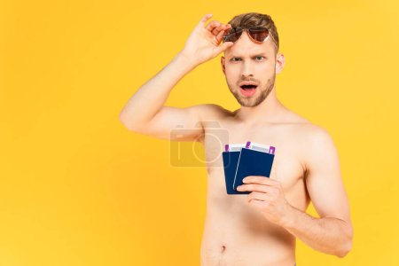 Photo for Shocked and shirtless man touching sunglasses and holding passports isolated on yellow - Royalty Free Image