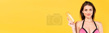 Photo for Horizontal concept of happy girl in swimsuit holding bottle with sunblock isolated on yellow - Royalty Free Image