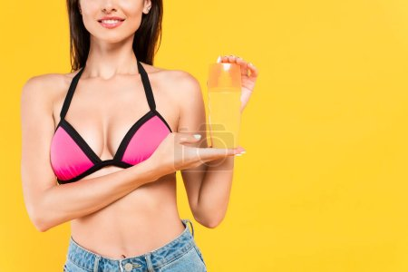 Photo for Cropped view of happy girl in swimsuit holding bottle with suntan isolated on yellow - Royalty Free Image