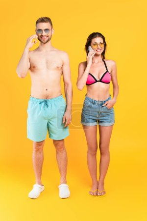 Photo for Cheerful couple in sunglasses and swimwear talking on smartphones on yellow - Royalty Free Image