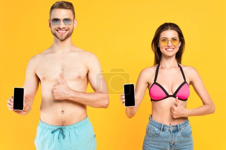 Photo for Happy couple in sunglasses and swimwear holding smartphones with blank screen and showing thumbs up isolated on yellow - Royalty Free Image
