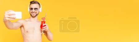 horizontal image of shirtless man in sunglasses and headphones taking selfie while holding cocktail isolated on yellow