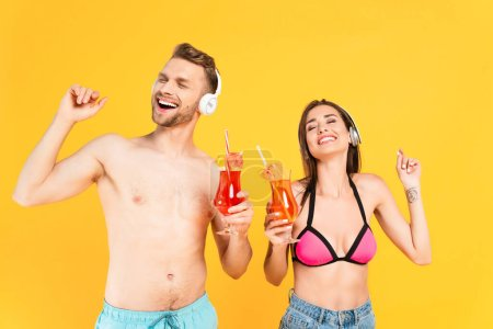 Photo for Happy man and woman in headphones holding cocktails isolated on yellow - Royalty Free Image