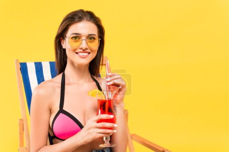 happy woman in sunglasses holding cocktail while sitting on deck chair isolated on yellow