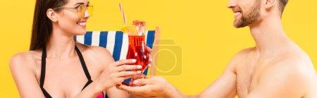 cultivo panorámico de barbudo hombre celebración cóctel cerca atractiva y feliz chica en gafas de sol aisladas en amarillo