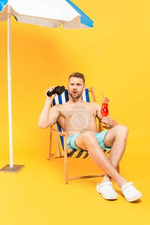 Photo for Surprised shirtless man holding cocktail and binoculars while sitting on deck chair on yellow - Royalty Free Image