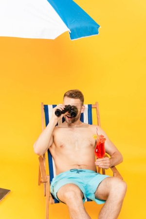 Photo for Happy shirtless man holding cocktail and looking through binoculars on yellow - Royalty Free Image