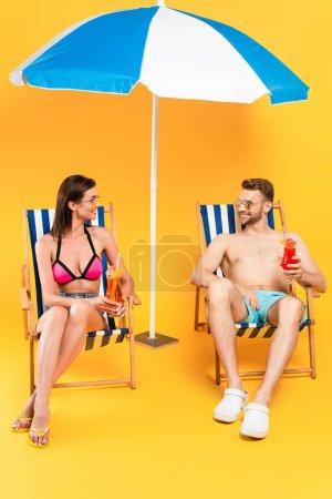 Photo pour Couple joyeux dans des lunettes de soleil tenant des cocktails tout en étant assis sur des chaises longues près du parasol sur jaune - image libre de droit
