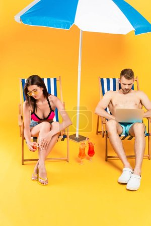 Photo for Shirtless man using laptop near woman sitting on deck chair and applying sunscreen on yellow - Royalty Free Image