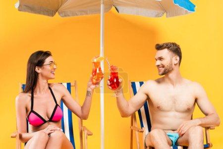 Photo pour Heureux couple cliquetis cocktails et assis sur des chaises longues près du parasol sur jaune - image libre de droit